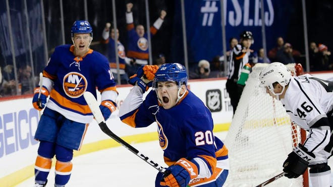 New York Islanders' Kieffer Bellows (20) celebrates after scoring his first NHL goal, as teammate Anthony Beauvillier, left, and Los Angeles Kings' Blake Lizotte, right, react during the second period of a hockey game Thursday, Feb. 6, 2020, in New York.