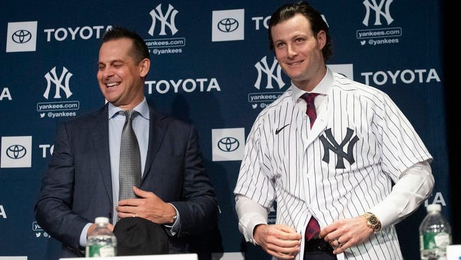 "From Dec. 18, 2019, New York Yankees manager Aaron Boone, left, smiles as Gerrit Cole tries on a Yankee jersey as he is introduced in New York. The pitcher agreed to a 9-year $324 million contract. ""He's going to be a game changer for us,"" Yankees owner Hal Steinbrenner said. ""The city's buzzing, and it's continued since the day we signed him."""