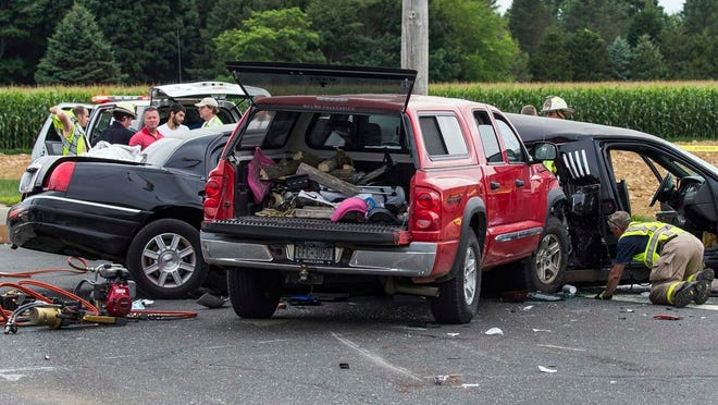FILE - In this July 18, 2015, file photo, authorities investigate the scene of a fatal crash between a limousine and sports utility vehicle in Cutchogue, N.Y. New York Gov. Andrew Cuomo has signed a package of limousine safety bills inspired by deadly crashes in 2015 and 2018. One of the bills signed Monday, Feb. 3, 2020, would require that motor vehicles converted into stretch limousines by January 2021 have at least two safety belts for the front seat and one safety belt in the rear for each passenger.