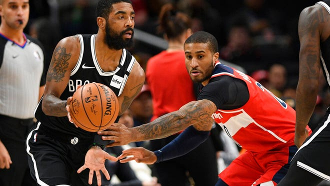 Brooklyn Nets guard Kyrie Irving, front left, dribbles the ball past Washington Wizards guard Gary Payton II, right, during the first half of an NBA basketball game, Saturday, Feb. 1, 2020, in Washington.