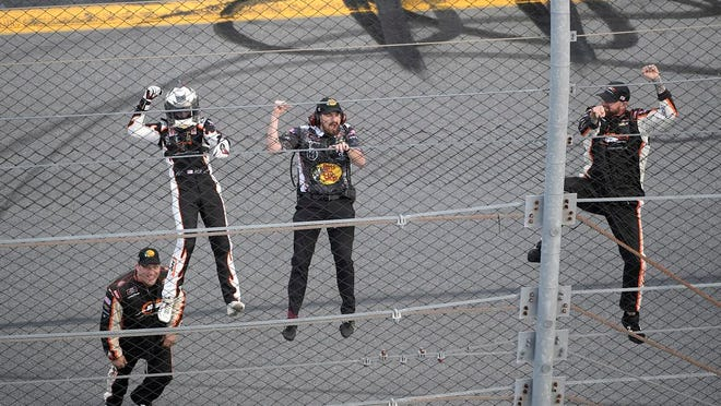 Noah Gragson, left, and crew members celebrate by climbing onto the grandstands safety fence after winning a NASCAR Xfinity series auto race at Daytona International Speedway, Saturday, Feb. 15, 2020, in Daytona Beach, Fla.
