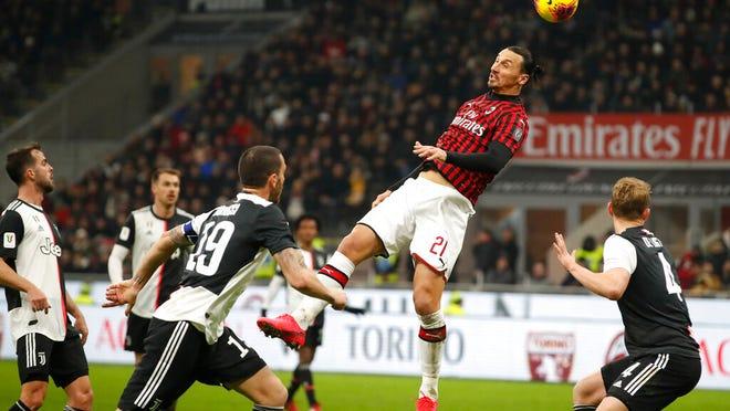 AC Milan's Zlatan Ibrahimovic, jumps for the ball by Juventus players during an Italian Cup soccer match between AC Milan and Juventus at the San Siro stadium, in Milan, Italy, Thursday, Feb. 13, 2020.