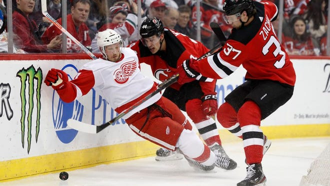 Detroit Red Wings defenseman Alex Biega (3) slips as New Jersey Devils center Pavel Zacha (37) tries to get control of the puck wiht Devils left wing Miles Wood (44) defending Biega during the second period of an NHL hockey game, Thursday, Feb. 13, 2020, in Newark, N.J.