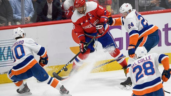 Washington Capitals left wing Alex Ovechkin (8), of Russia, and New York Islanders defenseman Scott Mayfield (24), left wing Michael Dal Colle (28) and Derick Brassard battle for the puck during the second period of an NHL hockey game, Monday, Feb. 10, 2020, in Washington.