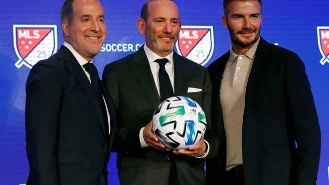Inter Miami CF co-owners Jorge Mas, left, and David Beckham, right, pose for photos with Major League Soccer Commissioner Don Garber during the Major League Soccer 25th Season kickoff event, New York, Wednesday, Feb. 26, 2020.