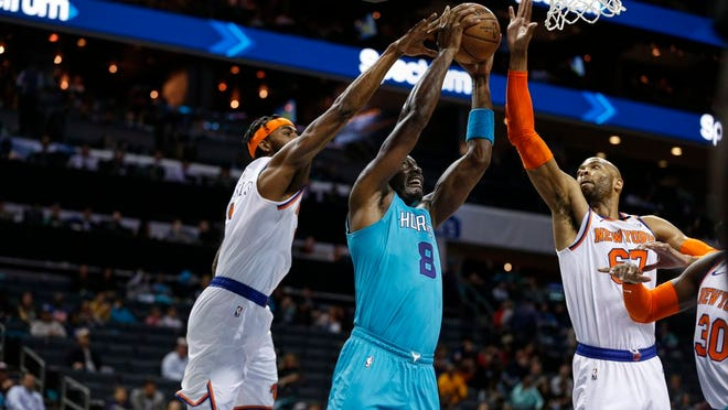 Hornets center Bismack Biyombo, center, goes up for a dunk between Knicks forward Maurice Harkless, left, and center Taj Gibson during the first half.
