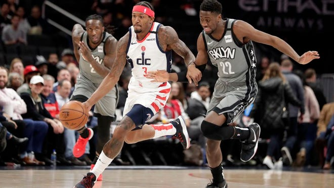 Wizards' Bradley Beal (3) moves the ball as Nets' Taurean Prince (2) and Caris LeVert, right, defend during the first half.