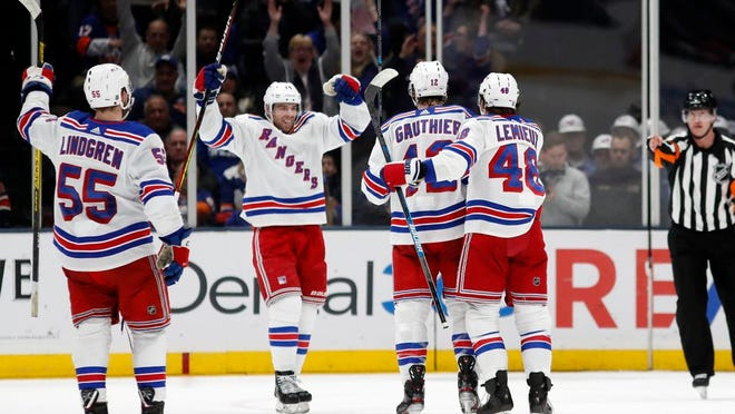 New York Rangers center Greg McKegg, second from left, celebrates with teammates after scoring a goal during the second period of an NHL hockey game against the New York Islanders, Tuesday, Feb. 25, 2020, in Uniondale, N.Y. Also shown are Rangers defenseman Ryan Lindgren (55), right wing Julien Gauthier (12) and left wing Brendan Lemieux (48).