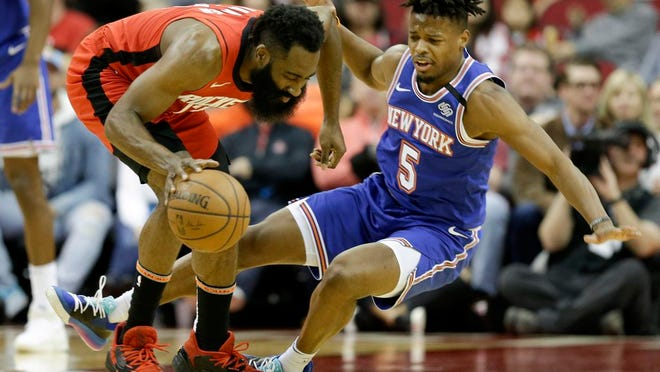 Houston Rockets guard James Harden, left, dribbles as New York Knicks guard Dennis Smith Jr. falls during the first half of an NBA basketball game, Monday, Feb. 24, 2020, in Houston.