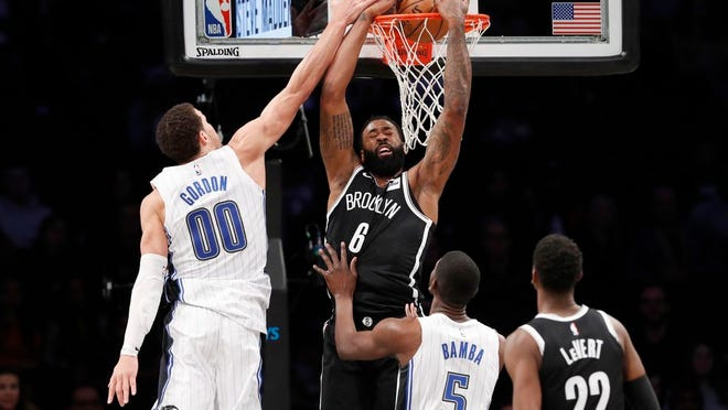 Brooklyn Nets center DeAndre Jordan (6) dunks as Orlando Magic forward Aaron Gordon (00) defends with Magic center Mo Bamba (5) and Nets guard Caris LeVert (22) watching during the second half of an NBA basketball game, Monday, Feb. 24, 2020, in New York.