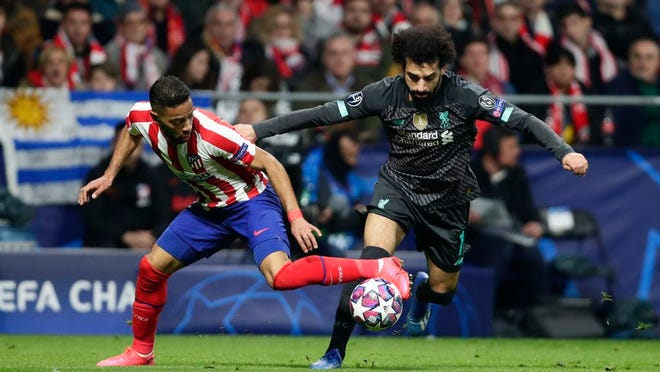 Atletico Madrid's Renan Lodi, left, and Liverpool's Mohamed Salah fight for the ball during a 1st leg, round of 16, of the Champions League soccer match between Atletico Madrid and Liverpool at the Wanda Metropolitano stadium in Madrid, Tuesday, Feb. 18, 2020.