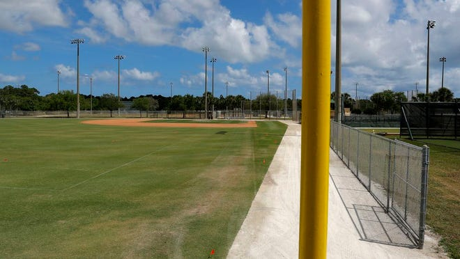 An empty practice field is seen at the Miami Marlins spring training baseball facility, Monday, March 16, 2020, in Jupiter, Fla. On Sunday night, the Centers for Disease Control and Prevention recommended gatherings of 50 people or more be canceled or postponed across the country for the next eight weeks. Major League Baseball planned to update teams Monday on its health policy.