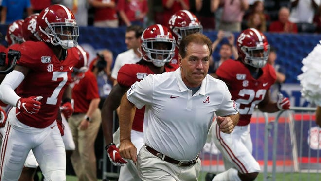 From Aug. 31, 2019, Alabama head coach Nick Saban leads his team onto the field for a an NCAA football game against Duke, in Atlanta. Around the country schools are taking the first cautious and detailed steps toward playing football through a pandemic, attempting to build COVID-19-free bubbles around their teams as players begin voluntary workouts throughout June. Thousands of athletes will be tested for COVID-19 _ though not all.