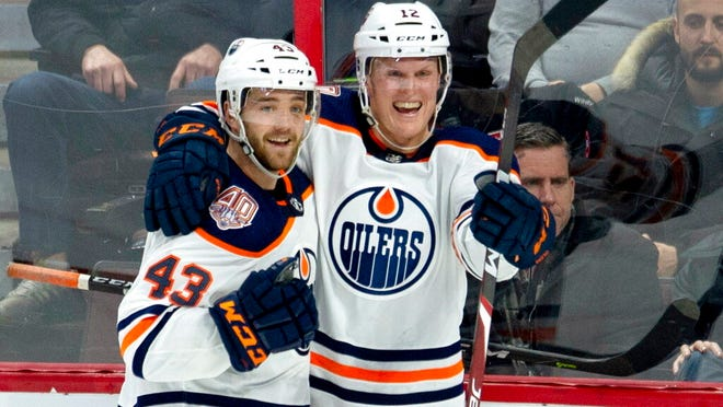 "From Feb. 28, 2019, Edmonton Oilers center Colby Cave (12), right, celebrating his goal with teammate Josh Currie during the third period of an NHL hockey game against the Ottawa Senators in Ottawa, Ontario. Edmonton Oilers prospect Cooper Marody has written a song in memory of teammate Colby Cave to raise money for a memorial fund. Cave, from Battleford, Saskatchewan, died April 11 in a Toronto hospital after suffering a brain bleed. He was 25. Marody's song ""Agape"" will be released Friday, June 12, 2020, on Apple Music and Spotify. Marody, from Brighton, Michigan, and Cave were teammates last season on the American Hockey League's Bakersfield Condors."
