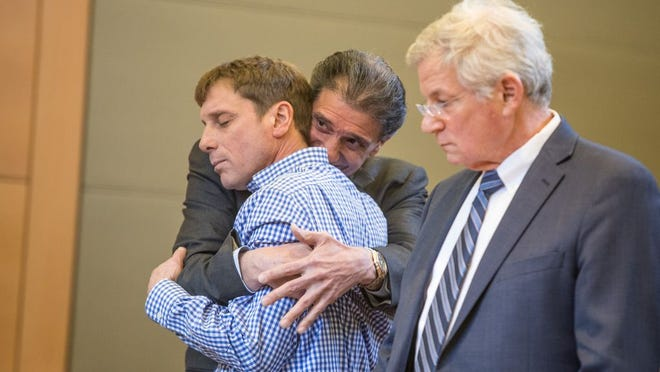 Attorney Michael Mazzariello, left embraces his client David Carlson, center after Carlson is cleared of all charges in Goshen, NY on January 16, 2020.