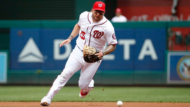 Washington Nationals first baseman Matt Adams fields a ground ball that was hit by New York Mets' Jeff McNeil in the first inning of a baseball game, Monday, Sept. 2, 2019, in Washington.