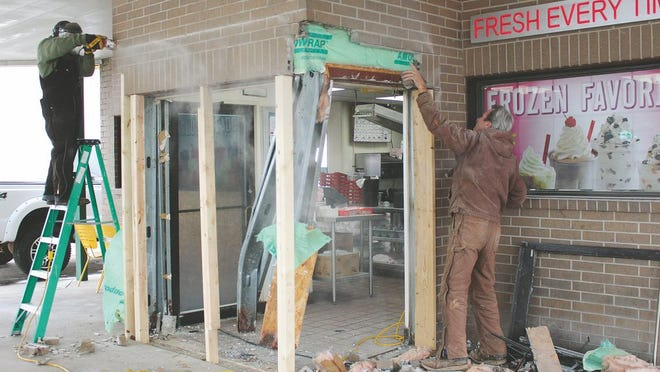 Jeff Pyles and Jeremy Howell (on ladder), of Pyles Custom Homes, LLC, work to repair damage to Sonic Drive-In on Thursday. A customer accidentally drove into the building Wednesday evening in Pratt.