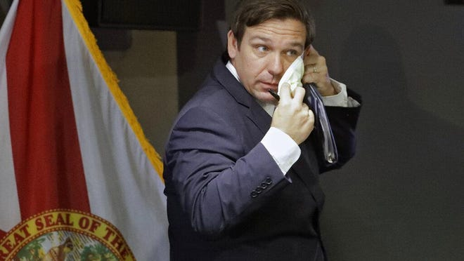 TAMPA -- Gov. Ron DeSantis puts on a safety mask after a COVID-19 news conference in April at the Tampa General Hospital. The governer has thus far, has refused to order a statewide mask mandate.