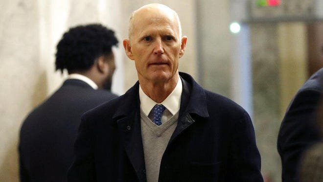 Sen. Rick Scott, R-Fla., arrives at the Capitol Hill in Washington, Tuesday, Jan. 21, 2020. President Donald Trump's impeachment trial quickly burst into a partisan fight Tuesday as proceedings began unfolding at the Capitol. Democrats objected strongly to rules proposed by the Republican leader for compressed arguments and a speedy trial.