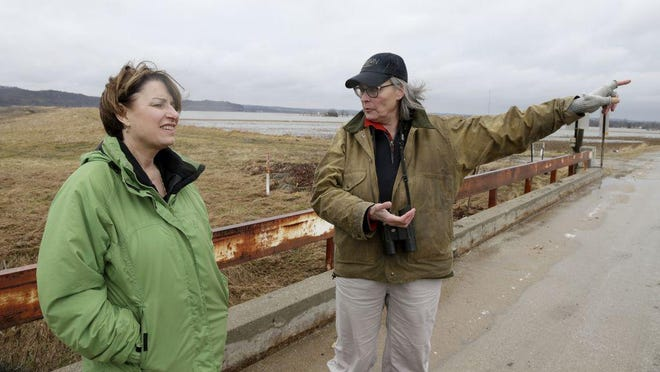 Resident Fran Parr, right, points out to 2020 Democratic presidential candidate Sen. Amy Klobuchar, D-Minn., the flooded areas around her home last month in Pacific Junction, Iowa.