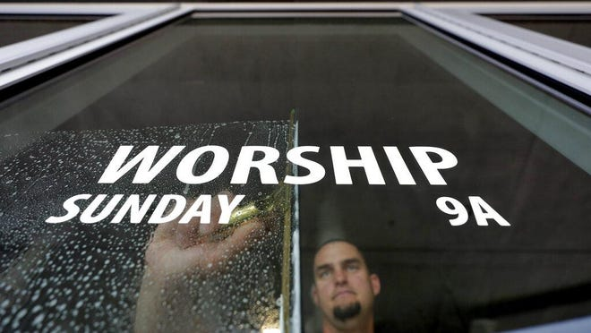 TEMPE, Ariz. -- Grace Bible Church facilities manager Kenny Sitton sanitizes entry door glass at the church on March 13, after church leaders participated in a state-wide conference call with Arizona Disease Control that highlighted the state's guidelines for preventing the spread of coronavirus in houses of worship.