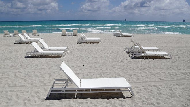 Empty chairs sit on the beach, Thursday, March 19, 2020, in Miami Beach, Fla.  Florida's largest county inched closer to economic shutdown as Miami-Dade County's mayor ordered all beaches, parks and non-essential commercial and retail businesses closed because of the coronavirus outbreak. Mayor Carlos Gimenez's order Thursday allows several businesses to remain open, including health care providers, grocery stores, gas stations, restaurants and banks.