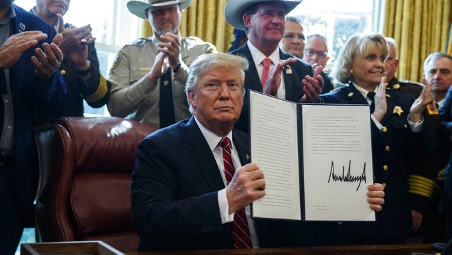 WASHINGTON -- President Donald Trump signs the first veto of his presidency in the Oval Office of the White House in March 2019. Trump issued the first veto, overruling Congress to protect his emergency declaration for border wall funding.