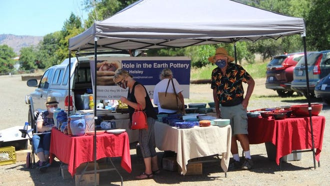 People enjoy shopping for bowls, vases and other creations at Hole in the Earth Pottery's booth at the Yreka Farmers Market last week.