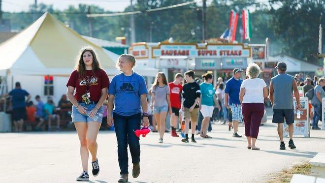 Fairgoers walk along through the Ashland County Fairgrounds during the fair on Saturday, September 21, 2019. Noelle Bye, Times-Gazette.com