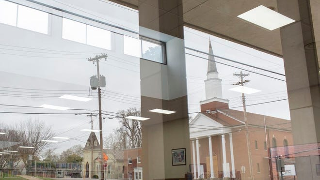 An empty North High Street is reflected in the windows of the closed Maury County Library as it remains shuttered in an effort to prevent the spread of the new coronavirus on Saturday, March 21, 2020.