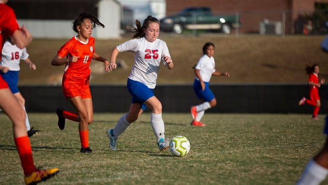 Mt. Pleasant Middle School forward Lillianne Jobe travels down the field pursued by opponents from Battle Creek Middle School during a tournament at Spring Hill High School on Friday, Sept., 27, 2019.