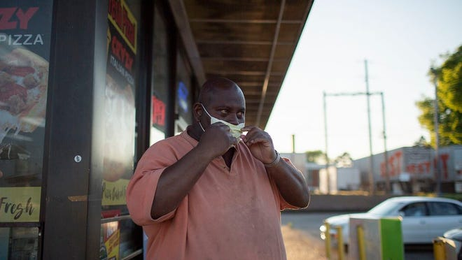 """Roland Stovall wears a protective surgical mask while taking a break in front of a Kwik Sak gas station convenience store in Columbia on Friday, April 10, 2020. """"People are dying,"""" Roland said. """"It is crazy out there."""" The previous day, a doctor at the nearby Maury Regional Medical Center announced that the local hospital had its first patient die from the COVID-19 virus. Data shows that the virus is disproportionately impacting minority communities."""