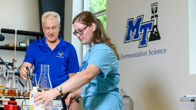MTSU Fermentation Science Director Tony Johnston, left, oversees as former student Kayley Stallings works with ingredients and chemicals in the lab at university partner Hop Springs in Murfreesboro in this 2019 file photo. A three-year, $300,000 U.S. Department of Agriculture grant is an MTSU partnership with Motlow State and Columbia State community colleges, to help recruit students to agriculture and fermentation science.