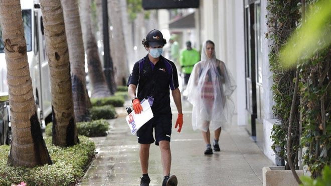 A FedEx worker wears a protective mask and gloves as he makes a delivery on Worth Ave. as shops prepare to open during the new coronavirus pandemic, Monday, May 11, 2020, in Palm Beach, Fla. Palm Beach County was authorized by Florida Gov. Ron DeSantis to initiate Phase 1 reopening regulations Monday, which includes limited reopening of retail establishments.