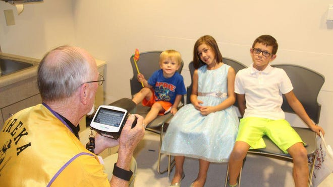 In this 2016 file photo, Yreka Host Lions Club member John Robak holds a vision screening camera while Malcolm, Larissa and Jonathan Davis await a screening.