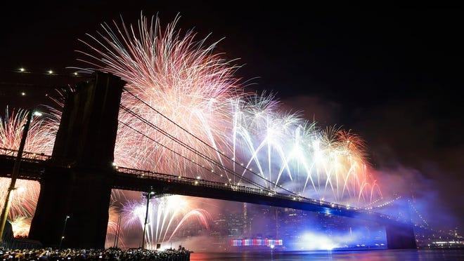 FILE- In this July 4, 2019 file photo, fireworks light up the sky above the Brooklyn Bridge during Macy's Fourth of July fireworks show in New York. This year's July 4th fireworks celebration will go forward in New York City, but with a twist meant to keep spectators from congregating in large numbers during the coronavirus pandemic.