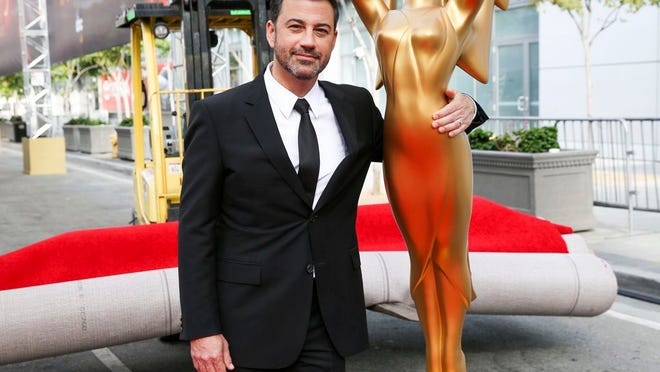 FILE - This Sept. 14, 2016 file photo shows host Jimmy Kimmel posing for a photo with a replica of an Emmy statue at the Primetime Emmy Awards Press Preview Day in Los Angeles. Kimmel will return as host and will serve as executive producer for the 72nd Emmy Awards. The show will be broadcast, Sunday, Sept. 20, on ABC.
