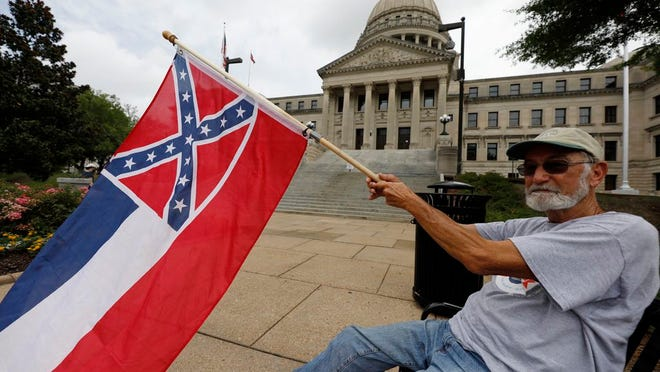 Larry Eubanks of Star waves the current Mississippi state flag as he sits before the front of the Capitol, Saturday, June 27, 2020, in Jackson, Miss. While a supporter of the current flag, Eubanks says he would hope lawmakers would allow a proposed flag change to be decided by the registered voters. The current state flag has in the canton portion of the banner the design of the Civil War-era Confederate battle flag, that has been the center of a long-simmering debate about its removal or replacement.