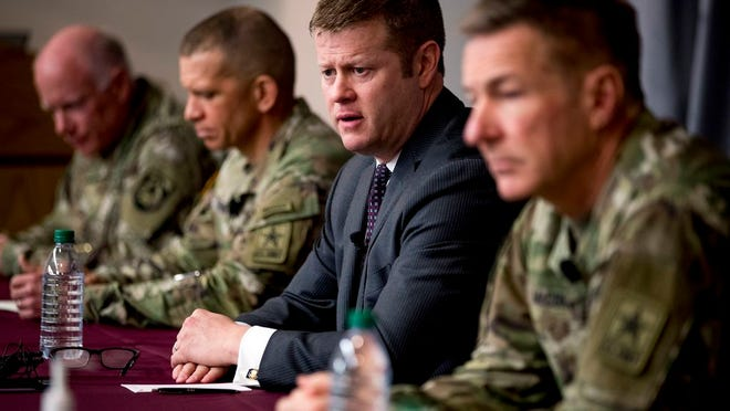 FILE - In this March 19, 2020, file photo Secretary of the Army Ryan McCarthy, center, accompanied by Col. Darrin Cox, left, Sgt. Maj. Michael Grinston, second from left, and Gen. James McConville, Chief of Staff of the Army, speaks at a news conference at U.S. Army Medical Research and Development Command at Fort Detrick in Frederick, Md. McCarthy announced Thursday, June 25, that beginning in August the service will no longer include soldiers' photos when they are being considered for promotion. He and McConville, said however, that they are still reviewing whether to redact the box on the form that identifies a person's race when soldiers are up for promotion.