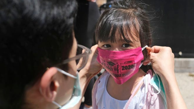 In this June 10, 2020, file photo, Olivia Chan's father helps her with a new mask she received during a graduation ceremony for her Pre-K class in front of Bradford School in Jersey City, N.J. School districts across America are in the midst of wrenching decisions during the summer about how to resume classes in settings radically altered by the coronavirus pandemic, with socially distanced school buses, virtual learning, outdoor classrooms and quarantine protocols for infected children as the new norm.