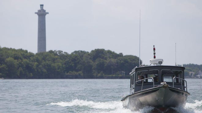 Perry's Victory and International Peace Memorial at Put-In-Bay is seen in the background as a boat travels from South Bass Island.