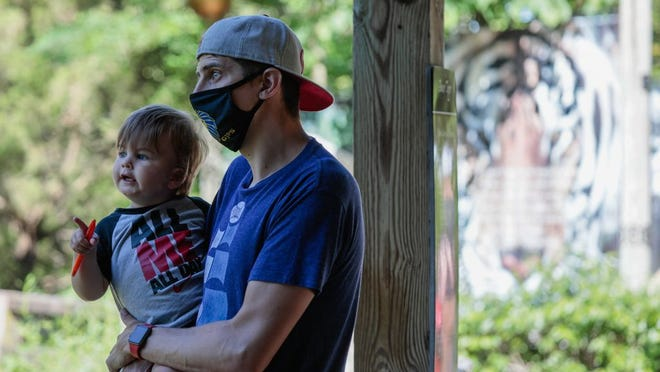 Paul Demchak of Gahanna wears a face mask as he holds his son, Brigham, 2, in June at the Columbus Zoo and Aquarium. A mayoral proclamation July 7 mandated facial coverings in the city, but it was superseded the next day by Gov. Mike DeWine's order that affects all of Franklin County.
