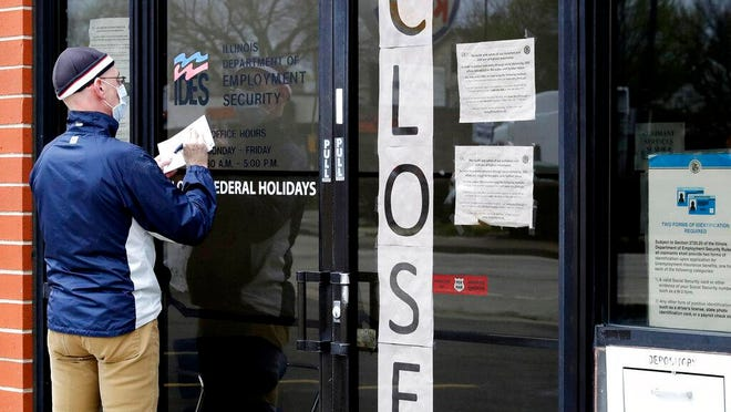 FILE - In this April 30, 2020 file photo, a man writes information in front of Illinois Department of Employment Security in Chicago. It's the paradox of a pandemic that has crushed the U.S. economy: There are 12.9 million job losses and a dangerous rash of closed business, yet the personal finances of many Americans have remained strong, and in some ways have even improved. A new poll by The Associated Press-NORC Center for Public Affairs Research shows that 45% of Americans say they're setting aside more money than usual. Twenty-six percent are paying down debt faster than they were before the coronavirus pandemic. In total, about half of Americans say they've either saved more or paid down debt. (AP Photo/Nam Y. Huh, File)