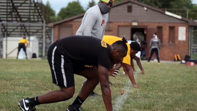 Beechcroft football coach Humphrey Simmons leads players, including junior Antwoin Reed Jr. (front), through defensive line drills during practice Aug. 4. Superintendent Talisa Dixon announced Aug. 13 that extracurricular activities were suspended for all Columbus City Schools, effective Aug. 14.