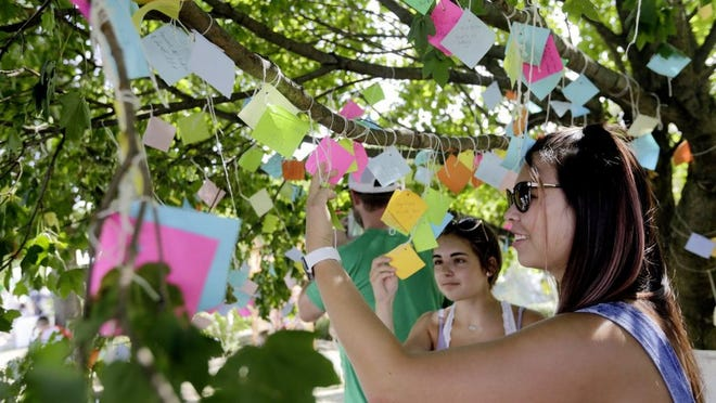 Emily Fu (right) of Columbus and Peyton Smith of Dublin read wishes left by guests on the Irish wishing tree during last year's Dublin Irish Festival at Coffman Park in Dublin. The annual festival drew more than 100,000 people. This year's festival was canceled because of the COVID-19 coronavirus pandemic.