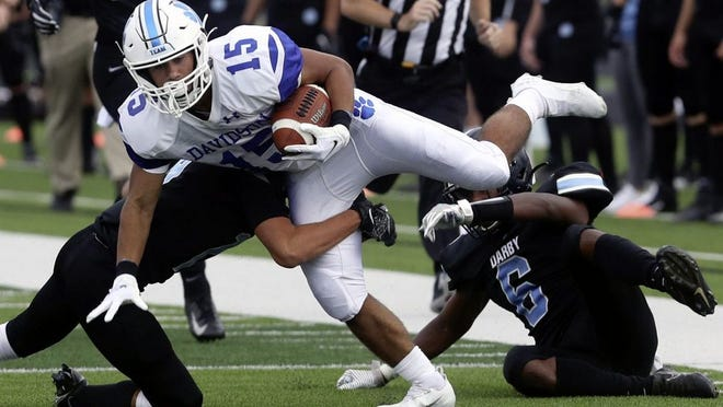 Hilliard Davidson's Leo Nixon is brought down by Hilliard Darby's Sam Buoni (19) and Eric Williams Jr. (6) during the season opener Aug. 27 at Darby. Davidson won 17-13.