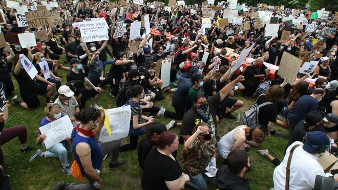 Protesters take a knee in Providence on Friday.