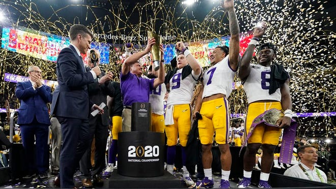 In this Jan. 13, 2020, file photo, LSU head coach Ed Orgeron holds the trophy after the team's victory over Clemson in an NCAA College Football Playoff national championship game in New Orleans.