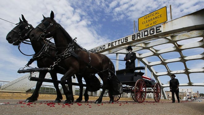 The casket of Rep. John Lewis moves over the Edmund Pettus Bridge by horse drawn carriage during a memorial service for Lewis, Sunday, July 26, 2020, in Selma, Ala. Lewis, who carried the struggle against racial discrimination from Southern battlegrounds of the 1960s to the halls of Congress, died Friday, July 17, 2020.