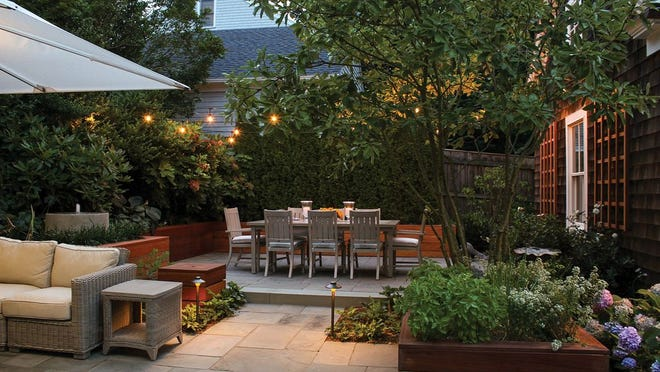 """Beds, borders, planters and levels help define the """"rooms"""" in Charlotte and Paul Marshall's Newport backyard. A discreet cylindrical fountain bubbles behind the sectional."""